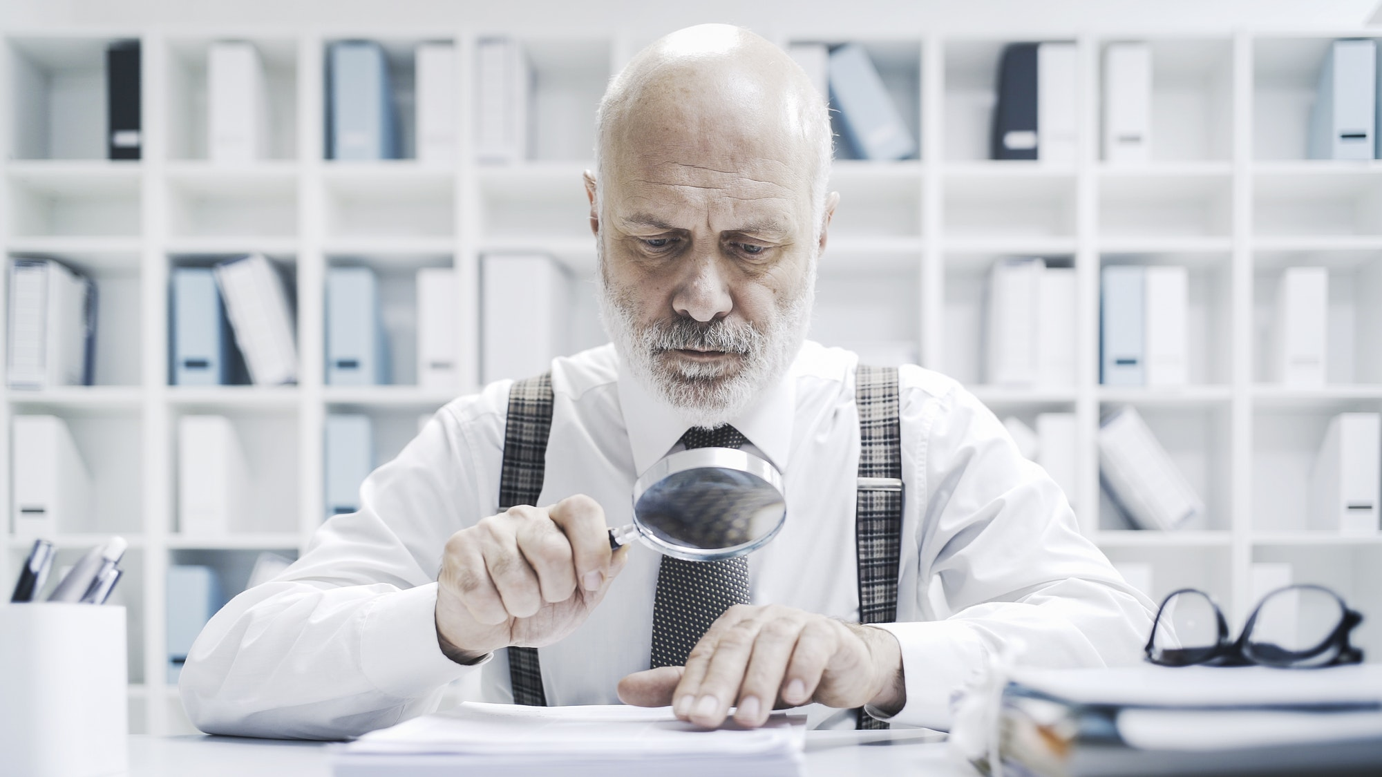 Corporate businessman checking paperwork with a magnifier