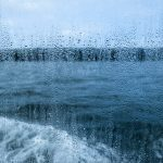 View through a rain spattered window over water and a boat's wake on an overcast day.